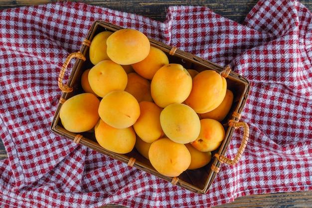 Aprikosen in einem korb auf picknicktuch und holztisch. flach liegen.
