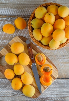 Aprikosen in einem korb mit messer draufsicht auf holz und schneidebrett