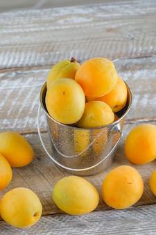 Aprikosen in einem mini-eimer auf holztisch, draufsicht.