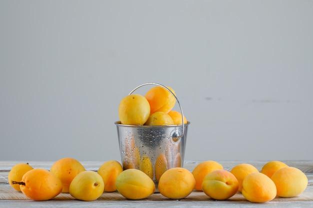 Aprikosen in einem mini-eimer auf holztisch, seitenansicht.