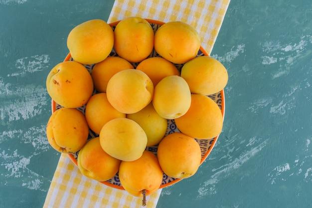 Aprikosen in einem teller auf gips und picknicktuch. flach liegen.