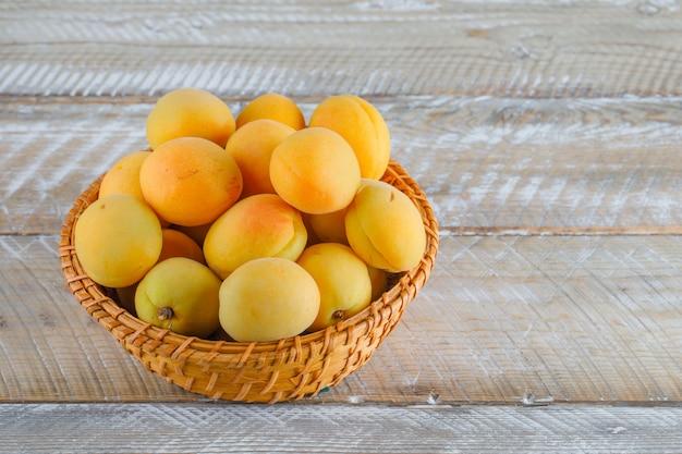 Aprikosen in einem weidenkorb auf einem holztisch. draufsicht.