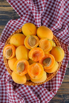 Aprikosen in einem weidenkorb auf holz- und picknicktuch. flach liegen.