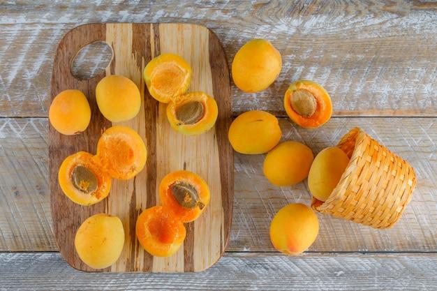 Aprikosen in einem weidenkorb auf holz und schneidebrett. flach liegen.