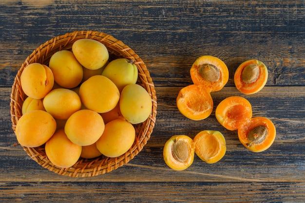 Aprikosen in einem weidenkorb auf holztisch, flach liegen.