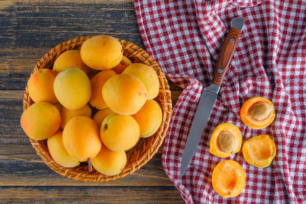 Aprikosen in einem weidenkorb mit flachem messer lagen auf picknicktuch und holztisch