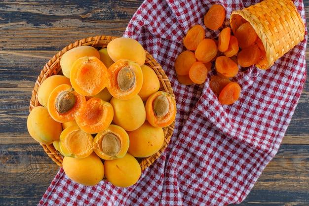 Aprikosen in einem weidenkorb mit getrockneten aprikosen lagen flach auf holz- und picknicktuch