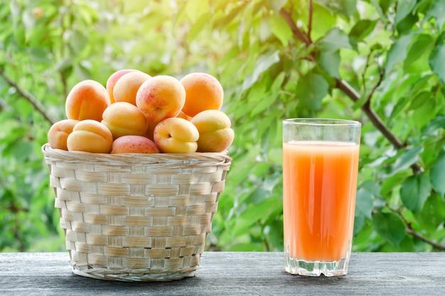 Aprikosen in einem weidenkorb und in einem glas saft auf einem grünen hintergrund, sonnenlicht