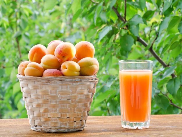 Aprikosen in einem weidenkorb und in einem glas saft