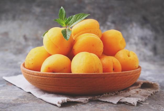 Aprikosen in einer hölzernen platte mit tadellosen blättern