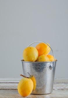 Aprikosen in mini-eimerseitenansicht auf holztisch