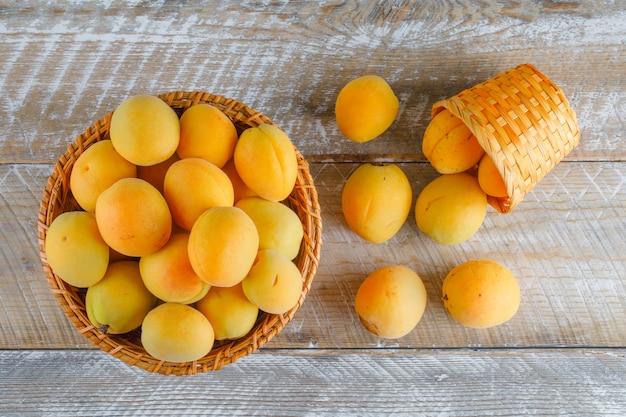 Aprikosen in weidenkörben auf einem holztisch. flach liegen.