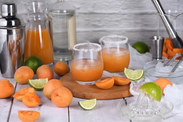Aprikosen-margarita - hergestellt aus frisch hergestelltem aprikosensaft, limettensaft und tequila. genießen sie diesen leichten, erfrischenden sommerparty-cocktail