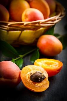 Aprikosen mit blättern auf dem alten holztisch