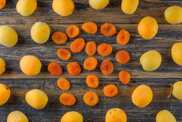 Aprikosen mit getrockneten aprikosen auf holztisch, flach gelegt.