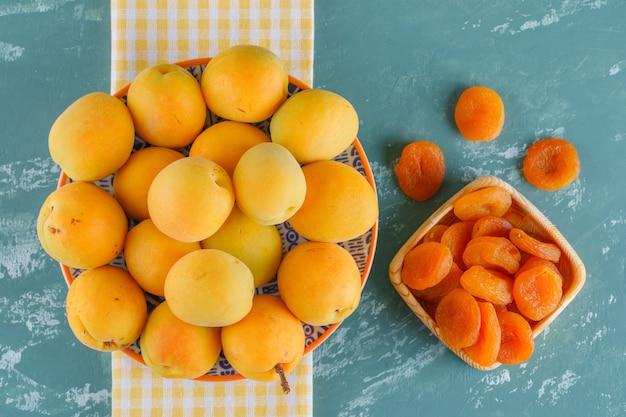 Aprikosen mit getrockneten aprikosen in einem teller auf gips und picknicktuch, flach gelegt.