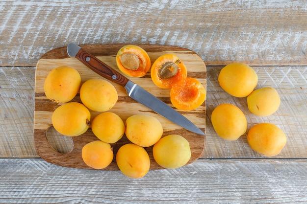 Aprikosen mit messer auf holz und schneidebrett, flach gelegt.
