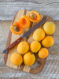 Aprikosen mit messer flach lagen auf holz und schneidebrett
