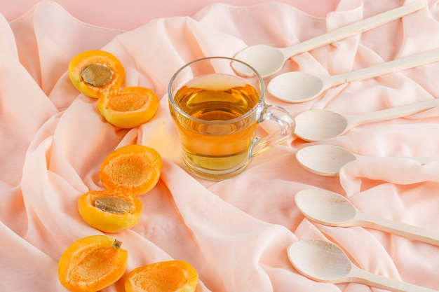 Aprikosen mit tee, holzlöffel draufsicht