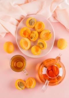 Aprikosen mit tee in einem teller, draufsicht.