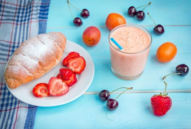 Aprikosen-smoothie in einem glas, croissant, reifen erdbeeren und kirschen.
