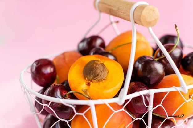 Aprikosen und kirschen im weißmetallkorb