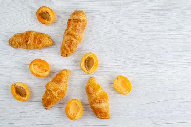 Aprikosencroissants von oben mit frischen aprikosen auf dem weißen schreibtischobstkuchen