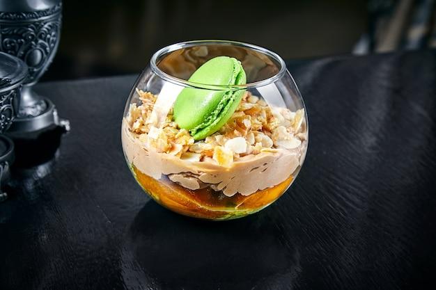 Aprikosendessert mit makrone in einem glas. pudding mit aprikose und mandel. schließen sie herauf süßes nahrungsmittelhintergrund mit kopienraum. dessertcreme mousse. selbstgemachter joghurt. aprikosenmarmelade und sahne