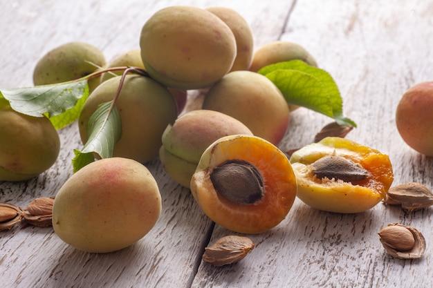 Aprikosenfrucht. frische organische aprikosen auf einem weißen hölzernen hintergrund. vega essen.