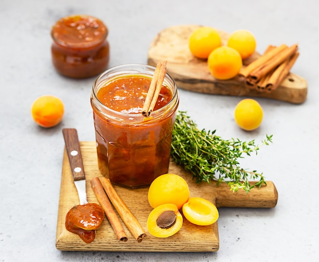 Aprikosenmarmelade in einem glas, frische aprikosen, thymian und zimt auf grauer oberfläche
