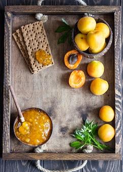 Aprikosenmarmelade in einer holzschale und frischen aprikosen. kopieren sie platz. sommerernte-konzept.