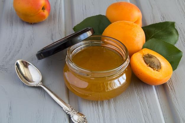 Aprikosenmarmelade und aprikosen auf dem grauen holz