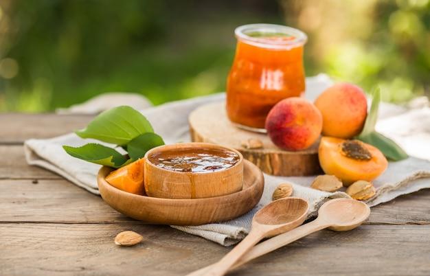Aprikosenmarmelade und reife aprikosen auf dem holztisch.