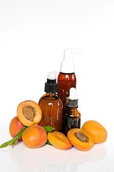 Aprikosenöl. aprikosenöl in einer glasflasche und reife aprikosen