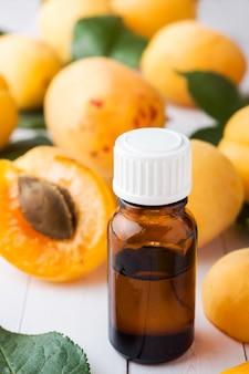 Aprikosenöl in einem glasgefäß mit nahaufnahme der frischen früchte auf dem tisch.