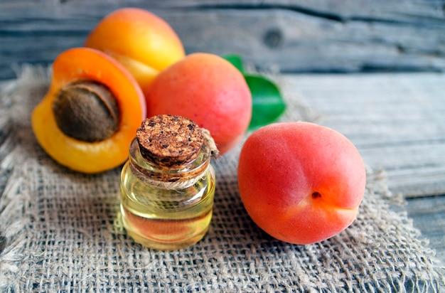 Aprikosenöl von den aprikosenkernen in einem glasgefäß und in frischen reifen aprikosen auf altem holztisch.