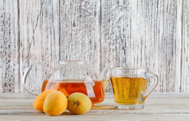 Aprikosentee in der teekanne und im glasbecher mit seitenansicht der aprikosen auf einem holztisch