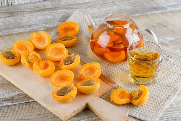 Aprikosentee in teekanne und becher mit aprikosen, schneidebrett draufsicht auf holz- und küchentuch