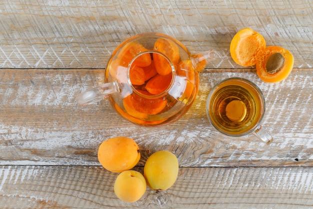 Aprikosentee in teekanne und glasbecher mit aprikosen-draufsicht auf einem holztisch