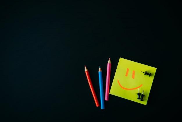 April narrentag feierkonzept. bürozubehör auf schwarzem hintergrund. unterschreiben sie auf einem stock.