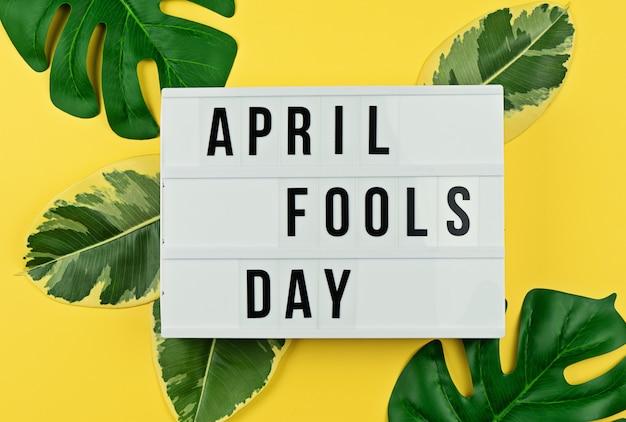 Aprilscherz und tropische blätter auf gelb