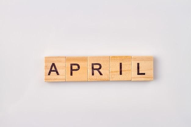Aprilwort geschrieben auf holzklötzen. auf weißem hintergrund isoliert.