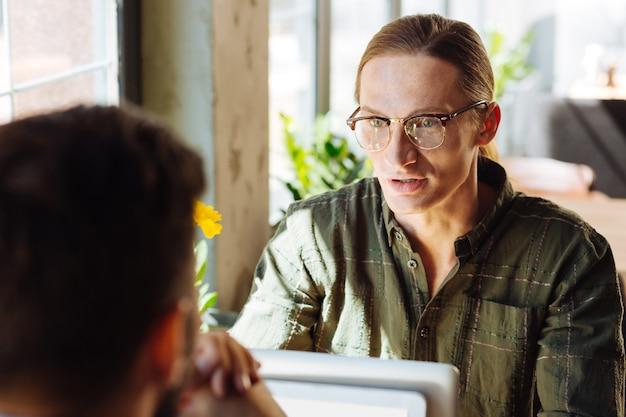 Apropos arbeit. nette positive männer, die am cafétisch sitzen, während sie sich dort zur arbeit treffen?