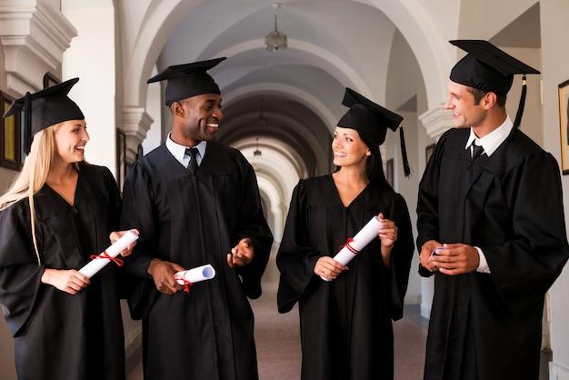 Apropos glänzende zukunft. vier hochschulabsolventen in abschlusskleidern gehen den universitätskorridor entlang und reden