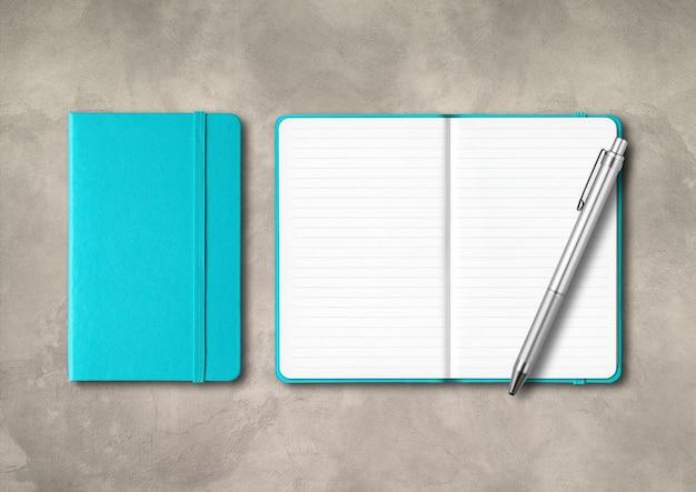 Aquablau geschlossene und offene notizbücher mit einem stift. isoliert auf konkretem hintergrund