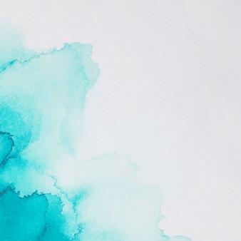 Aquamarin-flecken von farben auf weißem papier