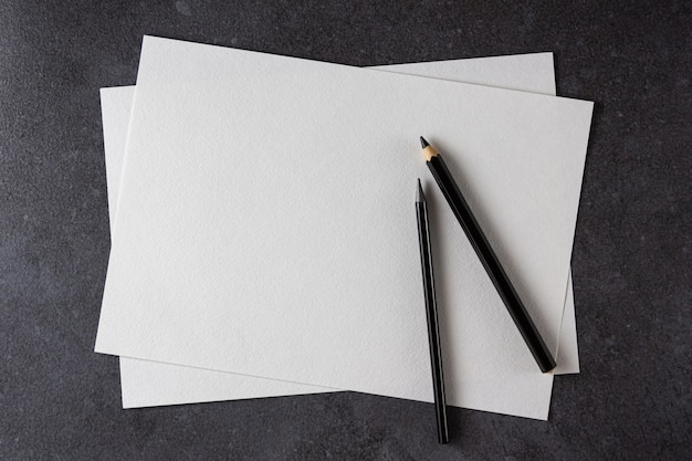 Aquarell a4 papier mit schwarzen stiften auf schwarz. draufsicht.