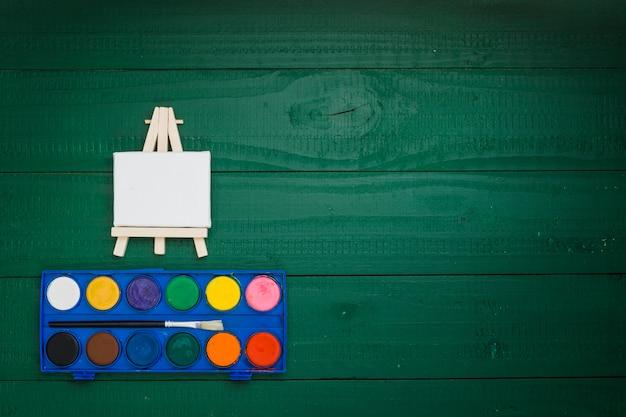 Aquarellausrüstung und miniaturgestell auf grünem hintergrund