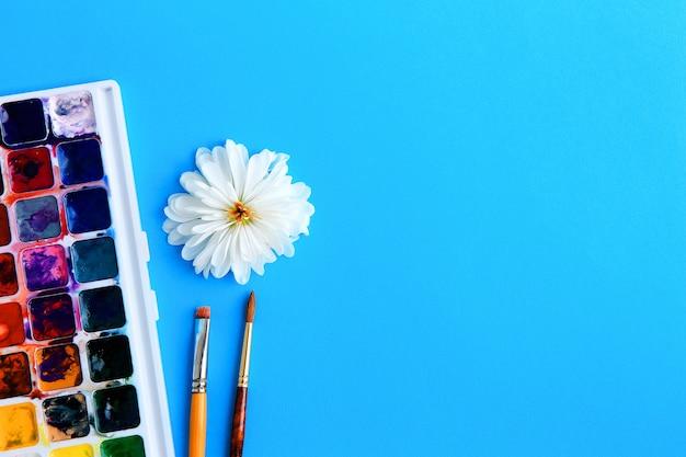 Aquarellfarbe, -pinsel und -blume mit weißen blumenblättern auf einem blauen hintergrundkonzept der kreativität