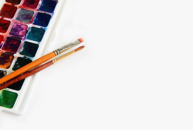 Aquarellfarbe und zwei bürsten auf einem weißen hintergrundkonzept der kreativität und der kunst